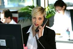 Frau am Schreibtisch mit Telefon Stockfotos