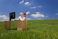 Frau am Schreibtisch unter Verwendung des Megaphons auf dem grünen Gebiet Lizenzfreie Stockfotos