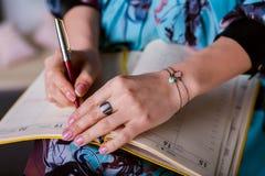 Frau schrieb eine Anmerkung in Tagebuch Lizenzfreie Stockbilder