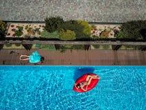 Frau schwimmt auf einem aufblasbaren Ruhesessel lizenzfreies stockbild