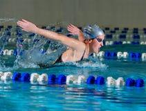 Frau schwimmt unter Verwendung des Basisrecheneinheitsanschlags Lizenzfreies Stockfoto