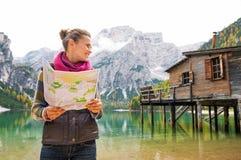 Frau am See Bries, das eine offene Karte und ein Lächeln hält Stockbilder