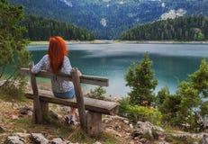 Frau setzt auf Bank und schaut auf dem See Lizenzfreie Stockbilder