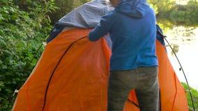 Frau setzt ein touristisches Zelt auf die Flussbank