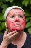 Frau setzt eine Schablone auf das Gesicht der Stachelbeere Stockfotografie