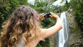 Frau setzt einen Fokus auf einen Smartphoneschirm und macht ein Foto eines Wasserfalls in einem Park stock video