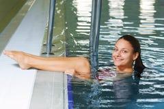 Frau setzt Fahrwerkbeine auf Poolrand Lizenzfreies Stockfoto