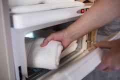 Frau setzt Tuch in elektrischen Trockner ein lizenzfreies stockbild