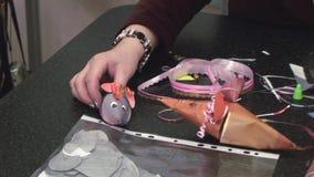 Frau setzte an die Tabellenmaus, die vom Papier gemacht wurde Scheren, Farbpapier, Markierungen liegen auf Tabelle liebhaberei stock video footage