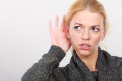 Frau setzte Hand zum Ohr für bessere Anhörung lizenzfreie stockfotografie