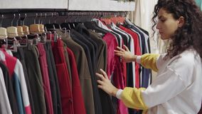 Frau sieht Kleidung im Verkauf im Geschäft, in beweglichen Aufhängern mit Hosen und in der Strickjacke an stock video footage
