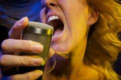 Frau singt mit Neigung Stockbild