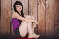 Frau sitzen hölzerne Hintergrundbeine des roten Stuhls oben lizenzfreie stockfotografie