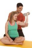 Frau sitzen Mann hinter Hilfen-fles Gewichten Lizenzfreies Stockbild
