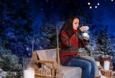 Frau, sitzend auf einem Schwingen mit einer Decke unter den Taschenlampen Stockbild