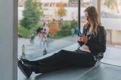 Frau sitzt auf Boden nahe Fenster, benutzt Smartphone Hippie-Mädchen, das auf Schirm des Telefons, blogging, Graseninternet schau Stockbilder