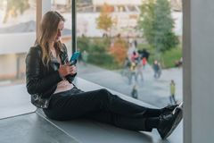 Frau sitzt auf Boden nahe Fenster, benutzt Smartphone Hippie-Mädchen, das auf Schirm des Telefons, blogging, Graseninternet schau Lizenzfreie Stockbilder