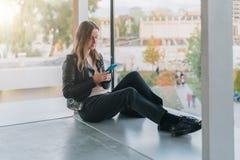 Frau sitzt auf Boden nahe Fenster, benutzt Smartphone Hippie-Mädchen, das auf Schirm des Telefons, blogging, Graseninternet schau Stockfotografie