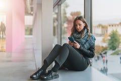 Frau sitzt auf Boden nahe Fenster, benutzt Smartphone Hippie-Mädchen, das auf Schirm des Telefons, blogging, Graseninternet schau Lizenzfreies Stockfoto