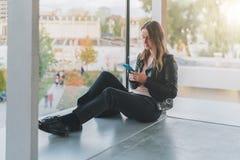 Frau sitzt auf Boden nahe Fenster, benutzt Smartphone Hippie-Mädchen, das auf Schirm des Telefons, blogging, Graseninternet schau Lizenzfreies Stockbild