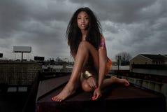 Frau sitzt auf Dachspitze in der Stadt Stockfotografie