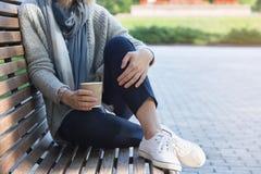 Frau sitzt auf der Bank und hält Kaffee Lizenzfreies Stockfoto
