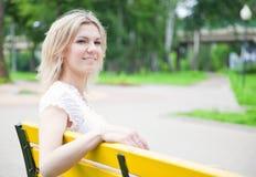 Frau sitzt auf der gelben Bank im Park Stockfotografie