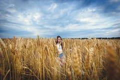 Frau sitzt auf einem Gebiet des Weizens und genießt Natur Stockbilder