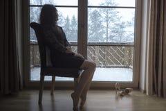 Frau sitzt auf einem Stuhl vor Glastüren Stockfoto