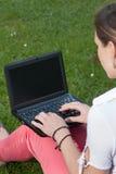 Frau sitzt auf einer Wiese mit einem netbook Stockbild