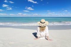 Frau sitzt auf Ozeanstrand in Kuba, tragender Hut, schöner Himmel und Wasser, stört nicht, perfekter Hintergrund, freier Raum stockfotografie