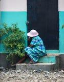 Frau sitzt auf Schritten zum Errichten in Robillard, Haiti lizenzfreie stockfotos