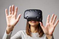 Frau sitzt auf Sofa At Home Wearing Virtual-Wirklichkeits-Kopfhörer Stockfoto