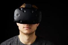Frau sitzt auf Sofa At Home Wearing Virtual-Wirklichkeits-Kopfhörer Lizenzfreie Stockfotos