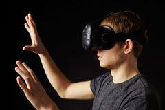 Frau sitzt auf Sofa At Home Wearing Virtual-Wirklichkeits-Kopfhörer Stockfotografie