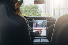 Frau sitzt drehen hinten herein Auto und elektronischen Armaturenbrett des Gebrauches Mädchenreisender, welche nach Weise durch N lizenzfreie stockfotografie