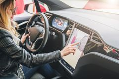 Frau sitzt drehen hinten herein Auto und elektronischen Armaturenbrett des Gebrauches Mädchenreisender, welche nach Weise durch N lizenzfreies stockfoto