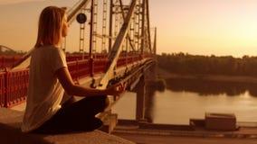 Frau sitzt durch die Brücke stock footage