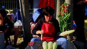 Frau sitzt Lächeln-Schalen-Maiskolben auf Straßenmarkt- in Vietnam stock footage