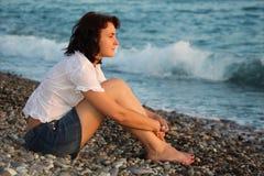 Frau sitzt an Land vom Meer stockfoto