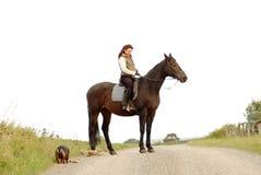 Frau sitzt rittlings auf einem Pferd auf weißem Hintergrund. Stockbild