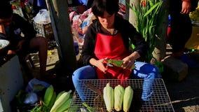 Frau sitzt Schalen-Verkaufs-Maiskolben auf Straßenmarkt- in Vietnam stock video