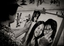 Frau skizziert ein Paar weibliche Gesichter von einer Fotografie lizenzfreie stockbilder
