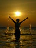 Frau am Sonnenaufgang mit Tropfen des Wassers Stockbild
