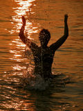 Frau am Sonnenuntergang im Meer Lizenzfreie Stockbilder