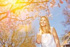 Frau am sonnigen Tag unter Kirschbaum im Frühjahr Lizenzfreie Stockfotos
