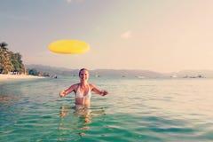 Frau spielt Frisbee im Wasser von schönem Ozean Lizenzfreie Stockfotografie