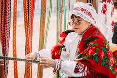 Frau in spinnendem Gurt des nationalen belarussischen Volkskostüms belarus Stockfotografie