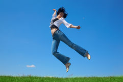Frau springen auf dem grünen Gebiet Lizenzfreie Stockbilder