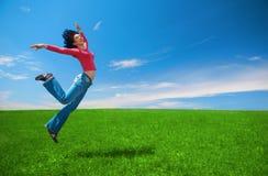 Frau springen auf dem grünen Gebiet Stockbild